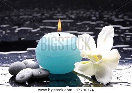 tiger's violet orchids and blue candle on water drops