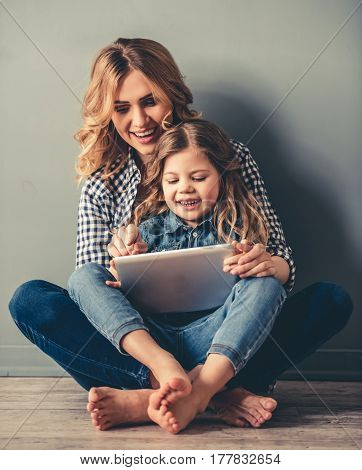 Cute little girl and her beautiful young mom are sitting together on the floor using a digital tablet and smiling on gray background