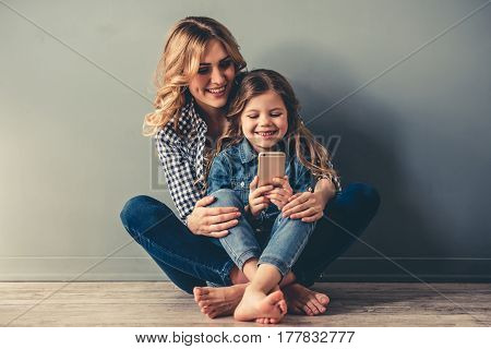 Cute little girl and her beautiful young mom are sitting together on the floor using a smart phone and smiling on gray background