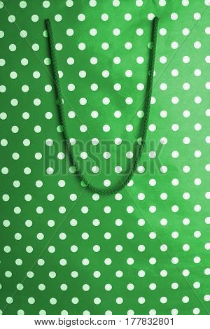 horizontal front view of green shopping bag background texture with polka dots and textile handle