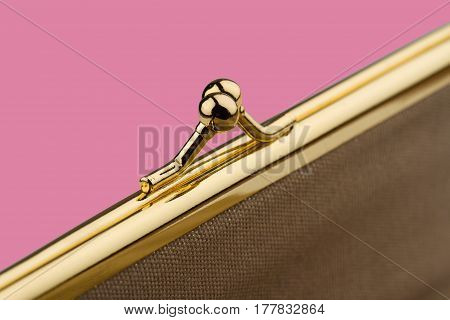 macro detail of closed female cream colored vintage wallet with golden metal enclosure on pink background