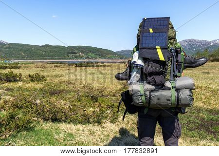 Solar charger over backpack in typical Scandinavian landscape