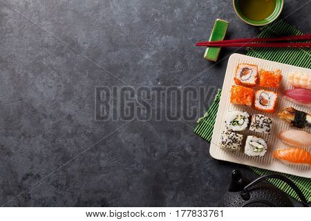 Set of sushi, maki and green tea on stone table. Top view with copy space