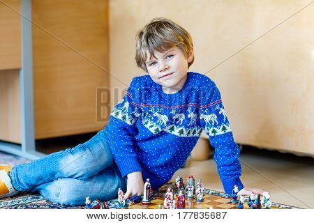 Little preschool kid boy playing chess game at home. child having fun with knight and soldier figures. Kid learning and thinking. Educational leisure for children at home.
