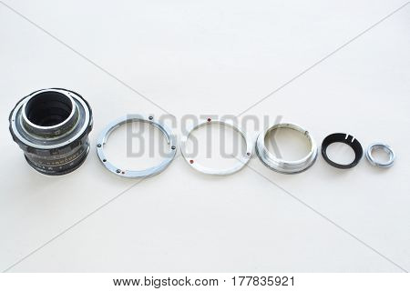 Details Of The Old Manual Lens, Free Space. A Disassembled Lens Lined Up In A Row On A White Backgro