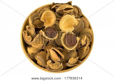 Closeup of seed and shell covers of Sacha inchi peanut, capsult fruit nut in a wooden bowl isolated on white background (Plukenetia volubilis)