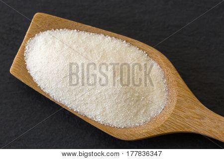 Wooden spoon full of dried white fine powder starch on dark stone background