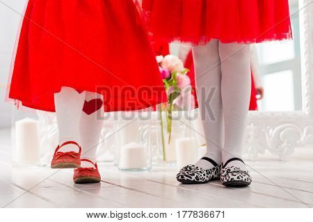 Legs in shoes two little girls in red dresses.