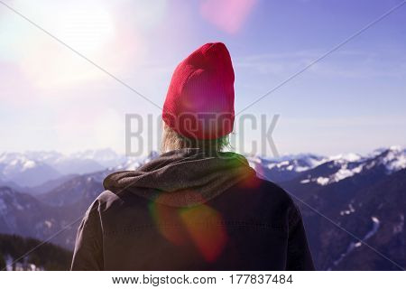 backside of young man with red cap looking into the distance surrounded by mountain peaks