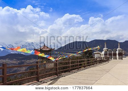 Scenery of Meili snow mountain with Prayer flags and Chinese style roof at the gate of Deqing city Yunnan China