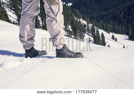 closeup of mans legs and boots in the snow surrounded by mountains