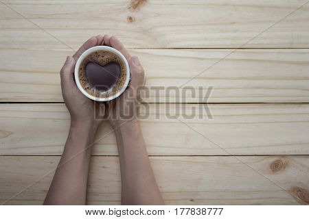 Coffee lover sign - man hands holding cups of coffee with heart shape on wooden table background. love symbol on fresh coffee mug in male hands - Top view with text space
