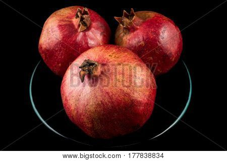 Three pomegranates on plate with black background