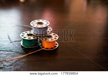 Bobbin thread color on wood table, blur