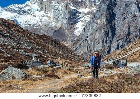 Mountain Valley with grassy and rocky sides vertical Walls of high Mountains and carefree Hiker walking on Footpath