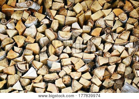 Natural wooden background closeup of chopped firewood. Firewood stacked and prepared for winter Pile of wood logs. Chopped firewood on a stack.