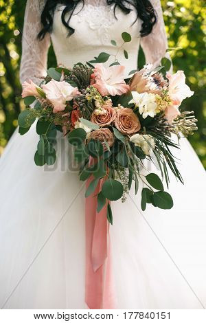 Wedding gentle disheveled bouquet of peach shades with pink ribbon in bridal hands