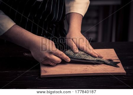 Chef cutting the fish on a board. Photo in brown tones. Kitchen. Wooden table. Hands of the cook close-up