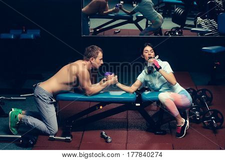 arm wrestling couple of pretty woman or cute girl and handsome guy or macho man with muscular torso and sexy body training in sport gym at trainer of weight lifting with water cups