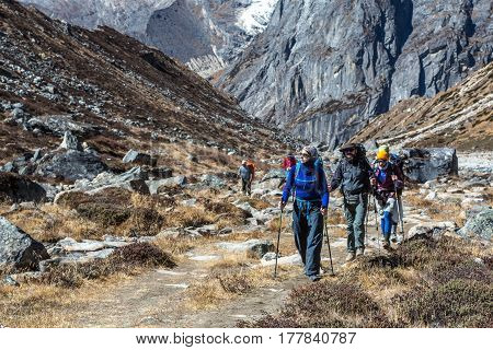 Sport Team of Mountain Climbers walking on Footpath among Rocks and Walls