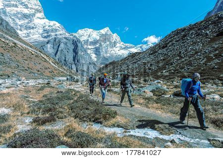 Sport Team of Mountain Climbers walking on Footpath among Rocks and Walls approaching to high Altitude Camp site during bright Spring Day toned undistractive Image