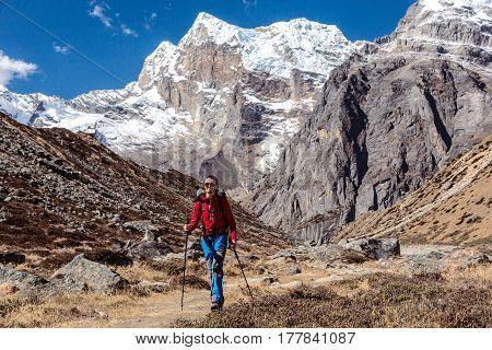Smiling slim Hiker in red sport Jacket and blue trekking Pants walking on grassy Footpath in high Mountains