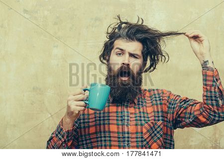 Surprised Bearded Man Pulling Stylish Fringe Hair With Blue Cup