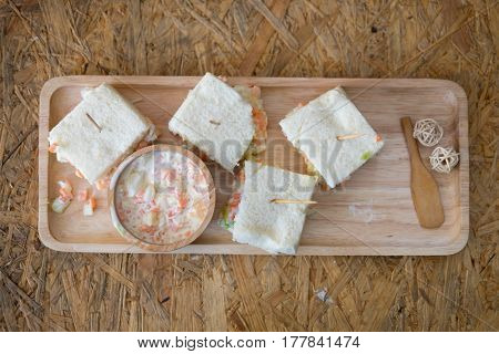 Sandwiches with coleslaw fillings and coleslaw salad on wood tray