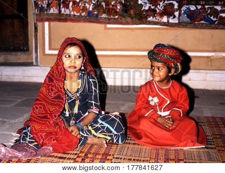 SAMODE, INDIA - NOVEMBER 22, 1993 - Young girl and boy in national dress sitting on a woven mat inside the Samode Palace Samode Rajasthan India, November 22, 1993.
