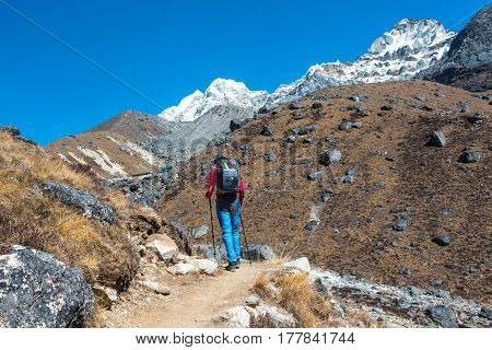 Mountain Hiker walking on Footpath in Nepal trekking carrying Backpack with Solar Panel attached for charging Battery of mobile Telephone snowy high altitude Summits and Peaks on Background.