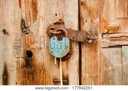 Old rusty padlock hanging on an old wooden door.