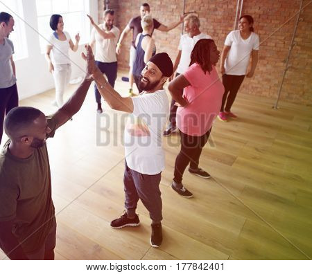 People training with trainer standing in room