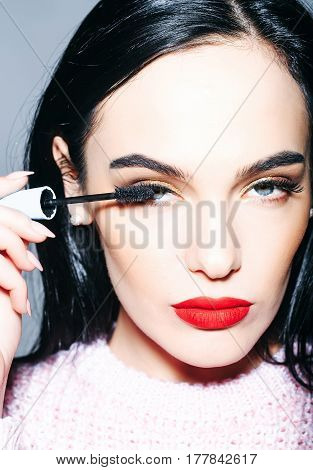 pretty woman or cute sexy girl with long curly brunette hair has red lips makeup on adorable face holds mascara brush near eyelashes