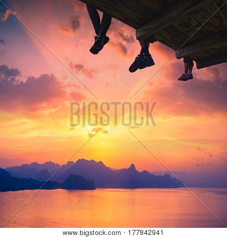Hikers sit on a wooden flooring above the Crimea sea bay with beautiful reflection of sun light at the water.