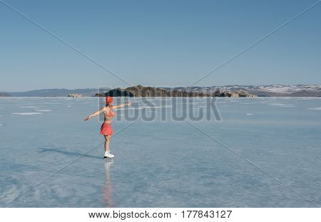 Girl extreme sportswear in a swimsuit on the ice. Ice lady. A female beginner skater skates and poses on skates, and tans. She has a beautiful body, strong health and great courage. It's freezing outside.