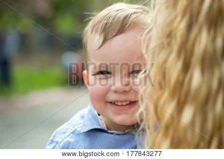 Cute happy baby boy little child with blond hair in blue shirt smiling in mother arms on summer sunny day outdoors on natural background