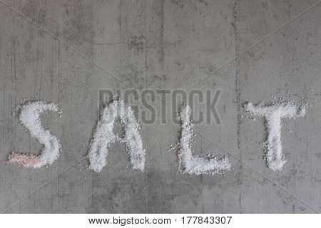 Word 'salt' written with real coarse salt on concrete background. Top copy space.