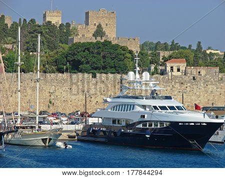 Harbor view with boats and yachts. In the background defensive walls of the Rodos castle