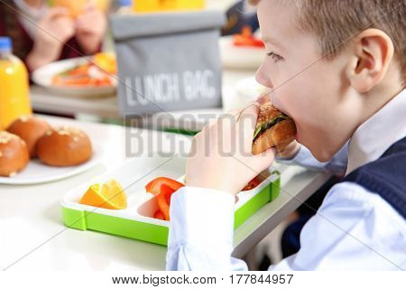 School boy eating sandwich while sitting at table in school cafeteria
