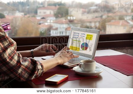 Freelancer working on Computer with Presentation Charts on screen at Roof Top Cafe sitting at wood Table next to Window with City View