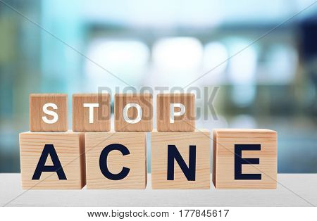 Text STOP ACNE of wooden cubes on table against blurred hospital background. Skin care concept