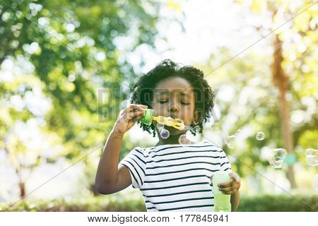 African girl blowing bubble in the park