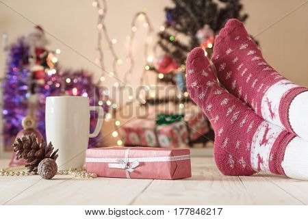 Christmas Eve Concept wooden floor with decorated gift package white mug and female foot in red socks with winter design. Christmas Tree and holidays illumination on Background