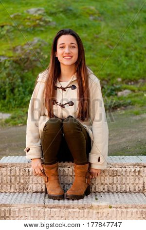 Pretty teenager girl sitting on the sidewalk in a park