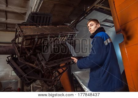 Molding Plastics In The Huge Factory Oven. Worker With The Laptop Is Controlling The Molding Process