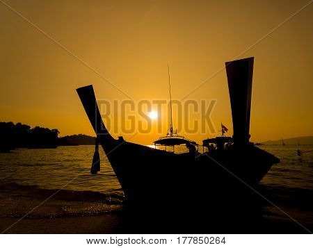 Silhouette Dark longtail boat on the beach over sunset