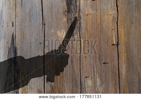 Humans hand with knife silhouette in shadow on wooden wall background with space for text or image.