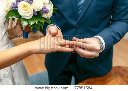 The groom puts on an engagement ring on the bride's finger.Horizontal photo