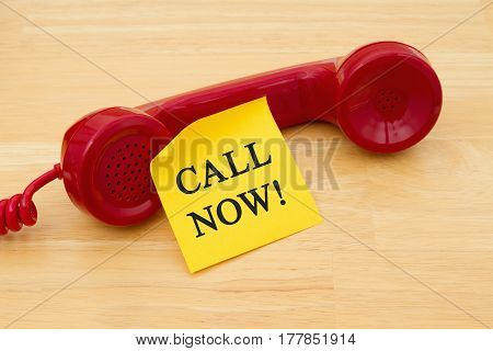 Call Now for assistance Retro red phone handset with a yellow sticky note and text Call Now