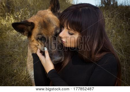 Girl and dog. Little girl with dog. Girl and dog meet each other. Big true love to pets, to dogs. Closeup portrait of beautiful girl and her lovely dog.Young happy with long dark hair hugging big dog.